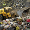 A worker piles garbage at the Commissioners Rd. waste transfer station in Toronto.