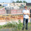 Residents stand in front of the site where construction of a controversial gas powered plant is underway in this July photo. Liberals announced today that construction of the plant will be halted if they are re-elected.